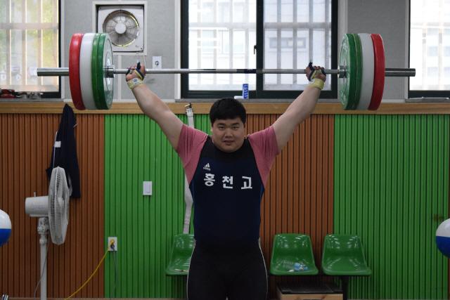 ▲ 송영환(18·홍천고) 선수가 홍천고 역도훈련장에서 바벨을 들어올리고 있다.