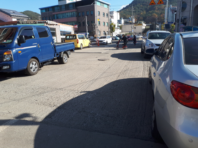 ▲ 4일 양구읍 산림조합 옆 도로에서 한 어르신이 타고 있던 전동차가 도로 절단면으로 통행이 불가능하자 수동으로 이동시키고 있다.
