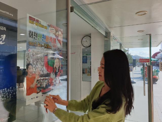▲ 화천군청 직원들이 4일 여주 고속도로 휴게소를 방문해 2020 화천산천어축제 홍보 포스터를 부착하고 있다.