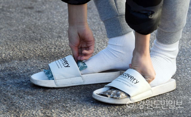▲ 수능 한파가 몰아친 14일 시험장인 춘천고에서 수험생을 응원 나온 한 재학생이 발에 핫팩을 대고 있다.  최유진