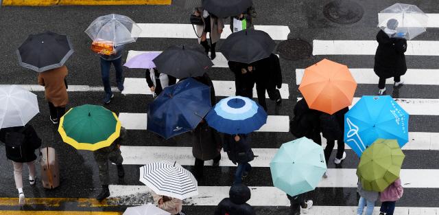 ▲ 겨울을 재촉하는 비가 내린 17일 춘천 명동에서 형형색색의 우산을 쓴 시민들이 건널목을 건너고 있다.기상청은 18일 오전까지 비가 온 뒤 기온이 크게 떨어질 것으로 전망했다.   최유진