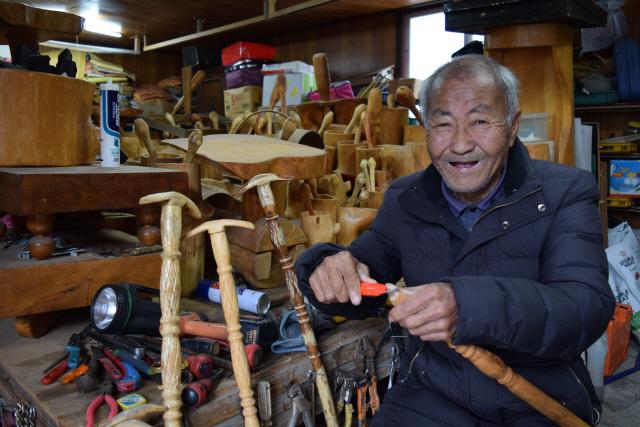 ▲ 이명우씨가 10일 자신의 집 창고에서 직접 만든 나무 지팡이를 선보이고 있다.