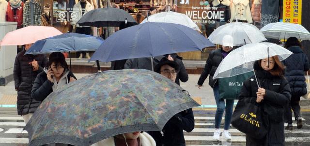 ▲ 겨울비가 내린 7일 춘천 명동에서 시민들이 우산을 쓰고 걷고 있다.  방병호