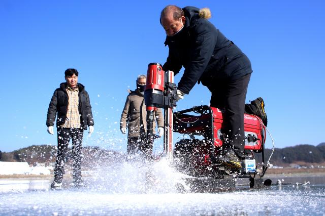 ▲ 제20회 인제빙어축제 개막을 앞둔 16일 축제장인 빙어호에서 관계자들이 빙어낚시를 위한 얼음구멍을 뚫고 있다.