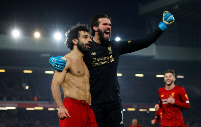"""▲ Soccer Football - Premier League - Liverpool v Manchester United - Anfield, Liverpool, Britain - January 19, 2020   Liverpool's Mohamed Salah celebrates scoring their second goal with Alisson   REUTERS/Phil Noble    EDITORIAL USE ONLY. No use with unauthorized audio, video, data, fixture lists, club/league logos or """"live"""" services. Online in-match use limited to 75 images, no video emulation. No use in betting, games or single club/league/player publications.  Please contact your account representative for further details. <All rights reserved by Yonhap News Agency>"""