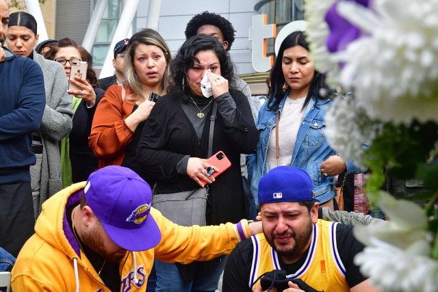 ▲ People gather around a makeshift memorial for former NBA and Los Angeles Lakers player Kobe Bryant after learning of his death at LA Live plaza in front of Staples Center in Los Angeles on January 26, 2020. - NBA legend Kobe Bryant died January 26, 2020 in a helicopter crash in suburban Los Angeles, celebrity website TMZ reported, saying five people are confirmed dead in the incident. (Photo by Frederic J. Brown / AFP) <All rights reserved by Yonhap News Agency>