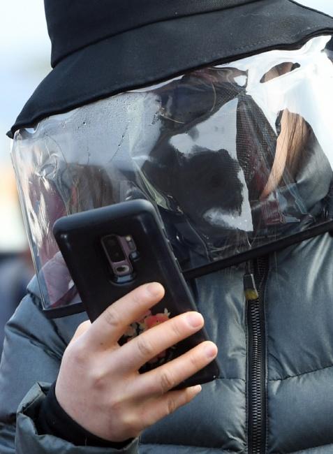▲ 2일 춘천 신북우체국에서 마스크를 구입하려는 한 시민이 마스크와 가림막 모자로 중무장한 채 대기하고 있다.    최유진
