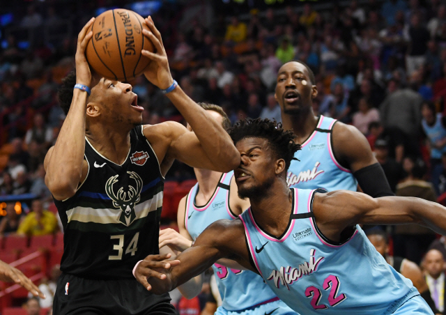 ▲ Mar 2, 2020; Miami, Florida, USA; Milwaukee Bucks forward Giannis Antetokounmpo (34) goes up for a shot against Miami Heat forward Jimmy Butler (22) in the first quarter at American Airlines Arena. Mandatory Credit: Jim Rassol-USA TODAY Sports