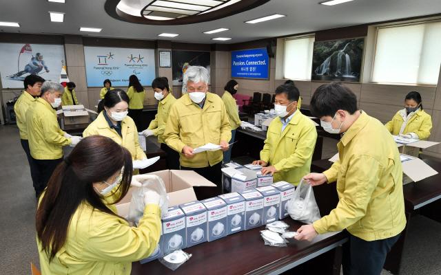 ▲ 최승준 정선군수와 공무원,자원봉사자들이 12일 북평면 행정복지센터에서 전 군민에게 배달하는 마스크를 포장하고 있다.